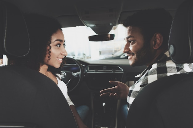 Guy and girl talk inside car choosing vehicle