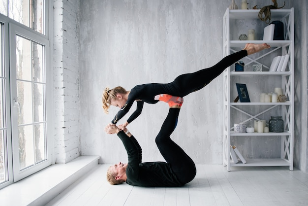 The guy and the girl in tracksuit. black sports uniform. male and female athletes. pumped up body. triathlon. morning work-out. set of exercises for body. classes in pair. workout together at home.