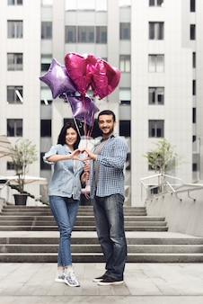 Guy and girl with balloons make heart hands shape.