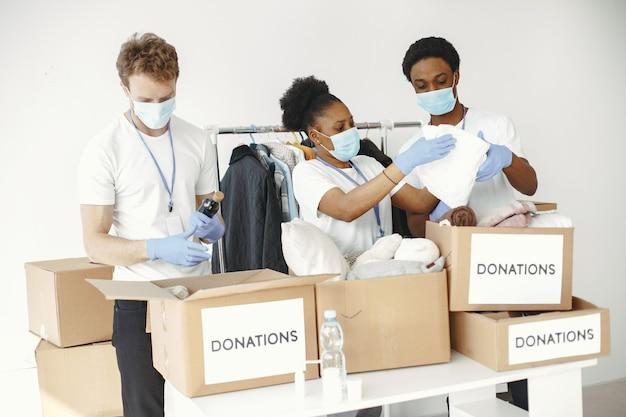 Ragazzo e ragazza con caselle di controllo volontari in maschere scatole con aiuti umanitari