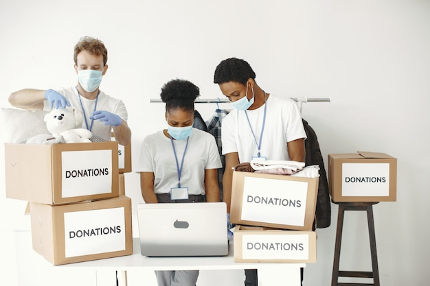 Guy and girl with check boxes volunteers in masks with laptop boxes with humanitarian aid