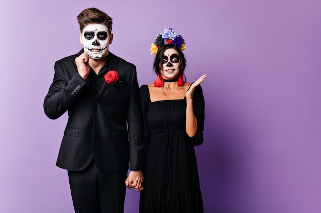 Guy and girl with painted faces are embarrassed, posing in purple studio. man and woman hold hands.