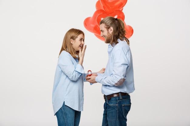 男は赤い心の風船と白い背景に女の子にリングを与える