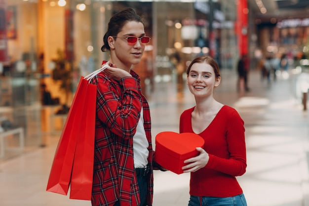 A guy gives his girlfriend a heart-shaped box in valentine's day. young couple at shopping mall.