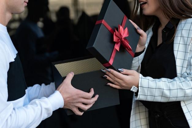 Парень дарит счастливой девушке подарок. с днем рождения, днем святого валентина.