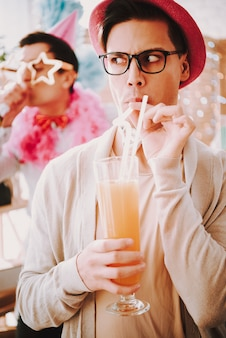Guy in glasses with a cocktail at a gay party.