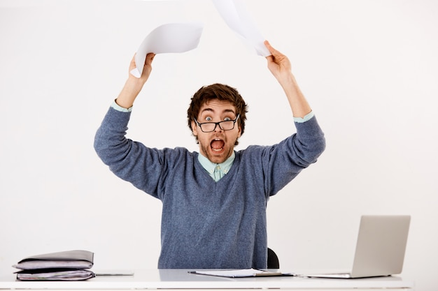 Guy going crazy with deadlines at work, tossing documents at reports, staring distressed and nervous, sit desk with laptop