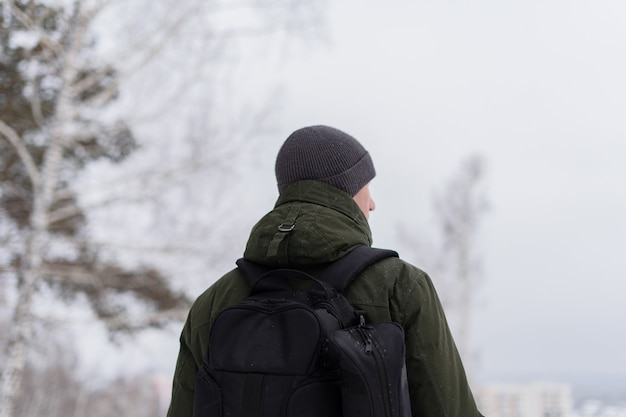 A guy in a green jacket and with a backpack stands with his back to the camera against the backdrop of the winter landscape