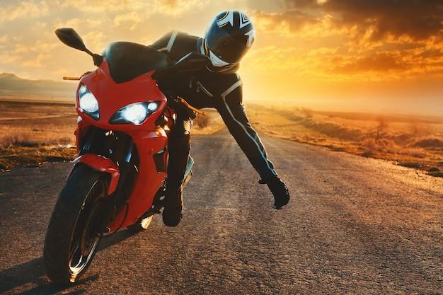 Парень приветствует в руке мотоцикл