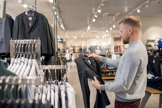 Guy in grey pullover holding hanger with black jacket while looking through sale collection in clothing department