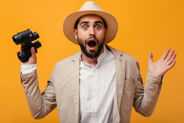 Guy in hat looks shocked into camera and holding binoculars