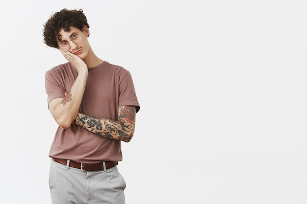 Guy hates sitting at home without action. portrait of bored handsome and stylish urban young male with moustache, tattooed arm and curly hair leaning on palm indifferent and gloomy