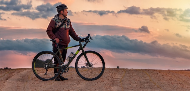 Guy in a helmet stands with a gravel bike in a sand field against a cloudy sky at sunset