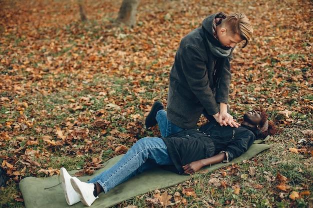 Парень помогите женщине. африканская девушка лежит без сознания. оказание первой помощи в парке.