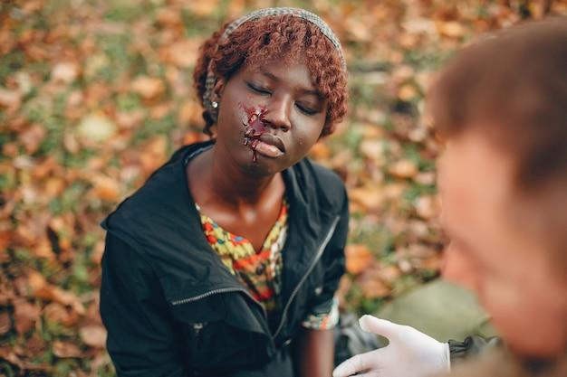男は女性を助けます。無意識に座っているアフリカの女の子。公園で応急処置を提供します。
