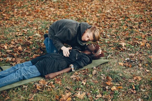 男は女性を助けます。アフロの女の子は無意識に横たわっています。公園で応急処置を提供する