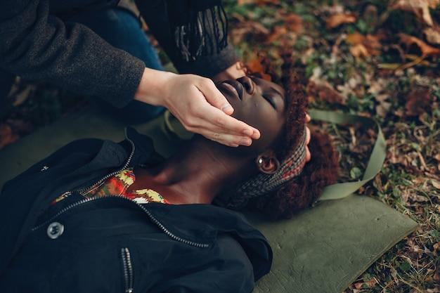 남자는 여자를 도와줍니다. 아프리카 소녀는 의식이없는 거짓말입니다. 공원 내 응급 처치