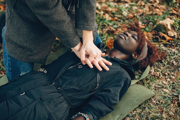 Guy help a woman. african girl is lying unconscious. providing first aid in the park.