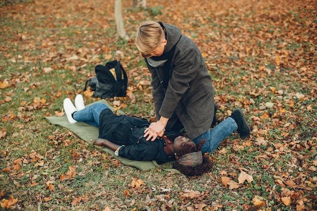 Guy aiuta una donna. la ragazza africana sta mentendo inconscia. fornire il primo soccorso nel parco.