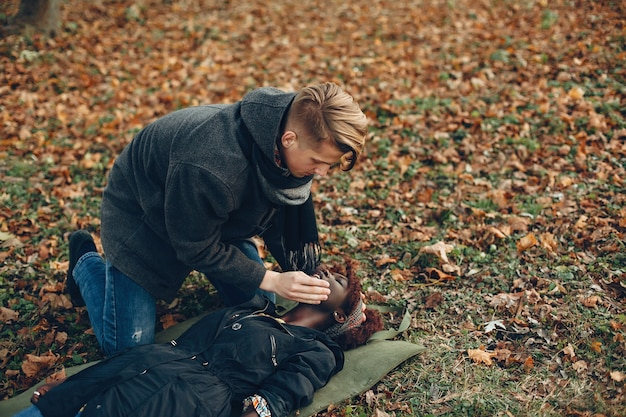 Guy aiuta una donna. la ragazza afro giace priva di sensi. fornire il primo soccorso nel parco