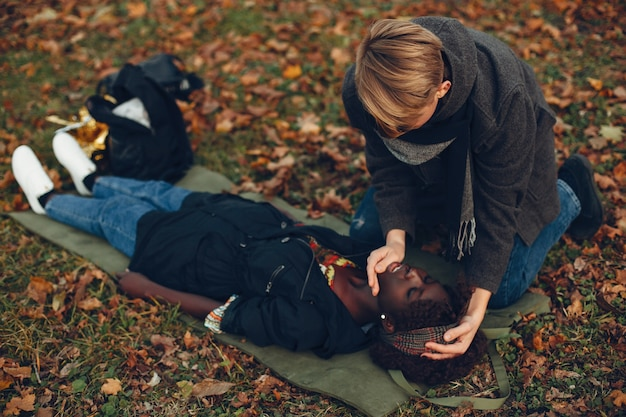 Guy help a woman. afro girl is lying unconscious. providing first aid in the park