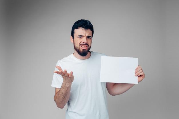 男はカメラに躊躇します。感情的な表現。白い空白のページを手に持ってください。ブルネットはうんざりしている。