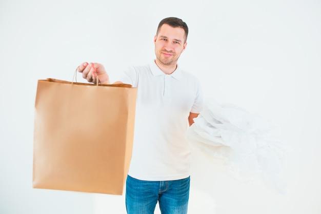 남자는 한 손에 비닐 봉지를 잡고 다른 한 손에 종이를 넣습니다. 재활용 과정 및 환경 관리. 책임있는 사용.