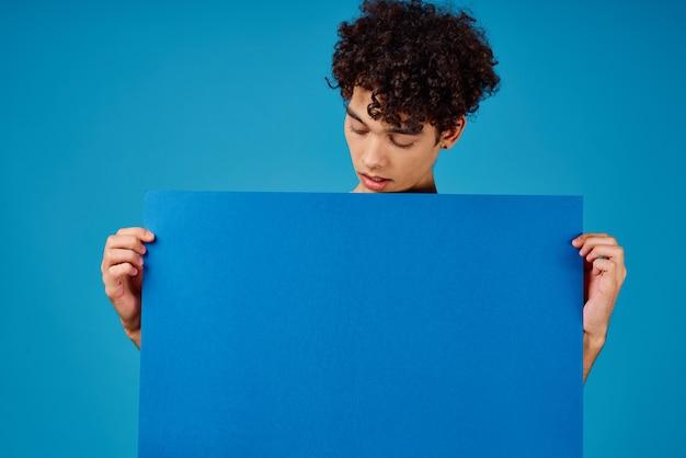 青いモックアップポスターコピースペーススタジオを保持している男