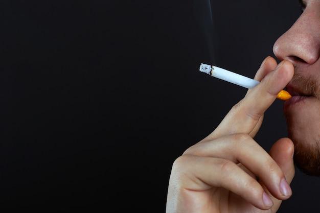 Парень с зажженной сигаретой дышит вредом курения от никотина.