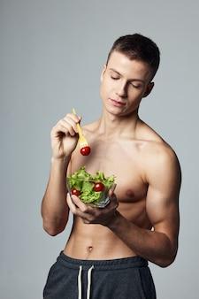 サラダ食品ダイエットエネルギー健康食品摂取のプレートを保持している男。