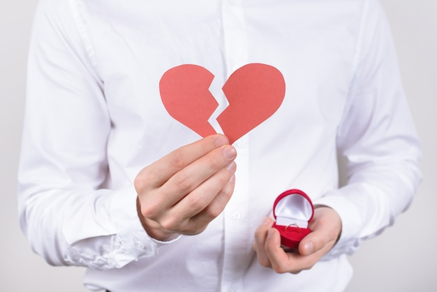 Guy holding broken paper heart and ring box