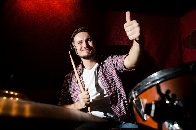 Guy holding a drumstick and giving a thumbs up