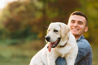 Guy holding his friend dog labrador and smiling at sunset
