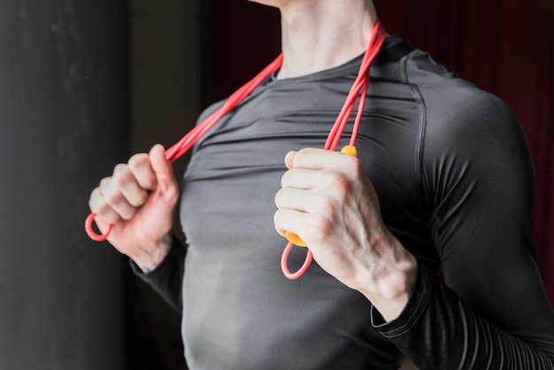 Guy holding jump rope laid on neck