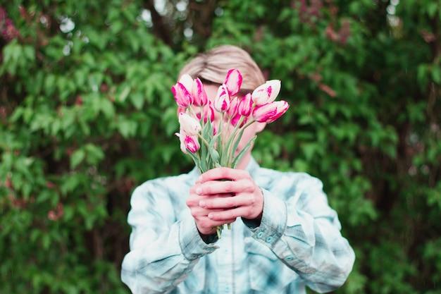 Парень держит букет тюльпанов, держа их перед собой