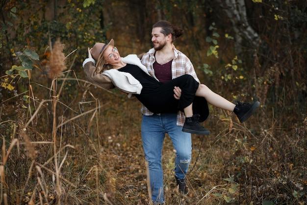 Парень держит девушку на руках на прогулке осенью