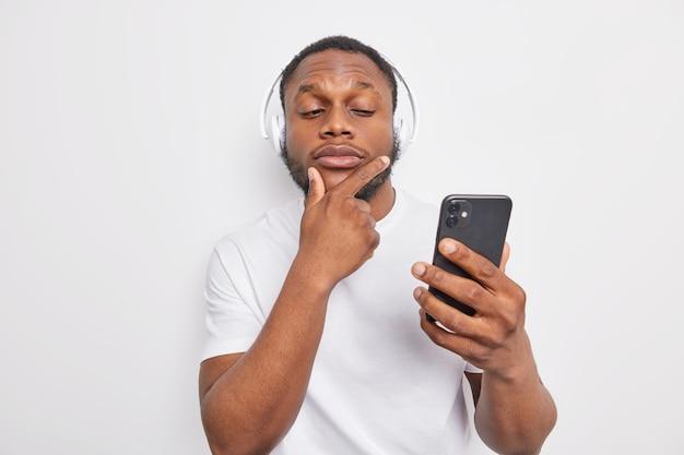 男はあごを持ってスマートフォンのディスプレイを注意深く見ますニュースを読みますオーディオトラックを選びます注意深く教育ポッドキャストを聞きますtシャツに身を包んだオーディオレッスン