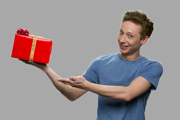 남자는 그의 손에 선물 상자를 보유하고 있습니다. 회색 배경에 선물 상자를 보여주는 십 대 남자. 겨울 휴가 축하.