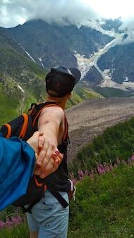 남자는 산에서 여자의 손을 잡고