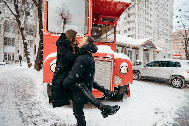 The guy holds his beloved girl in his arms against the background of a red bus