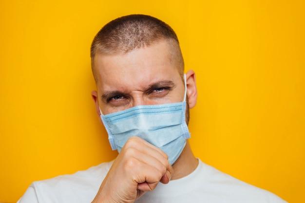 男は口の近くで拳を握り、喉が痛いことを示す咳をします。仮面の男がカメラを見ています。風邪、インフルエンザ、ウイルス、検疫、流行の概念。