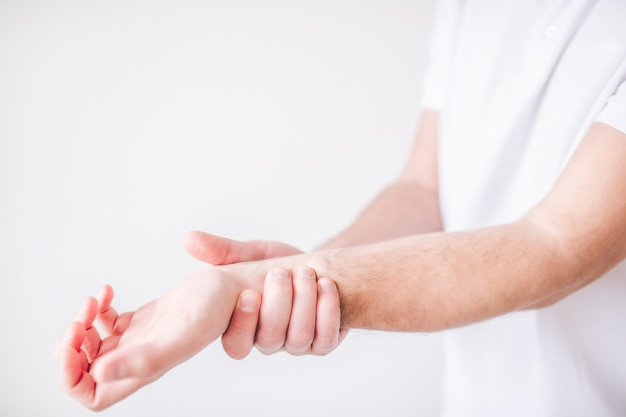 Guy holds his hand by the wrist because of pain and ache