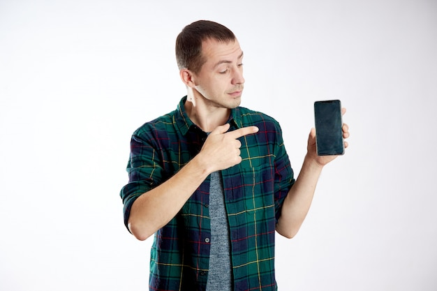 Guy holds the phone in his hands and points at it with his finger