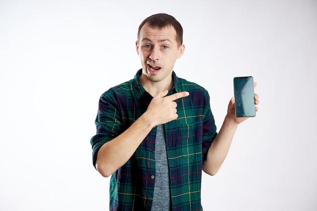 Guyは携帯電話を手に持ち、指でそれを指しています。男が電話で遊んで、ビデオやソーシャルネットワークを見る