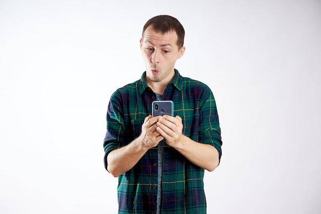 男は電話を手に持ち、指で指差します。男は自分の携帯電話で再生し、ビデオ、ソーシャルネットワークを見る