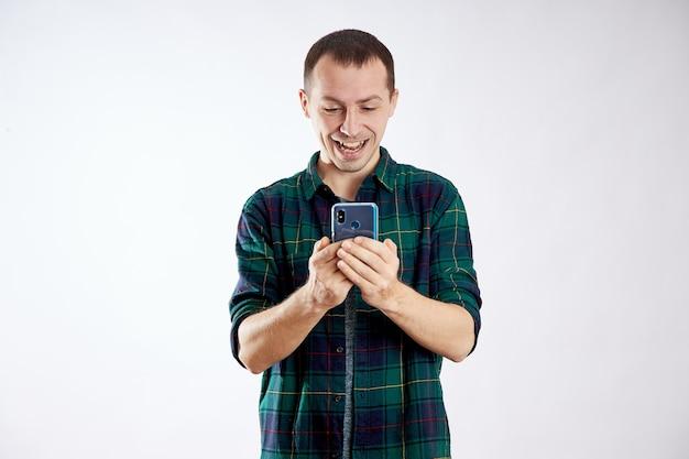 男は携帯電話を手に持って指で指さします。男は彼の電話で遊んで、ビデオ、ソーシャルネットワークを見ます