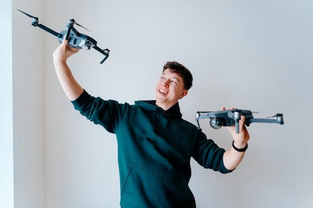 Парень держит два квадрокоптера у стены