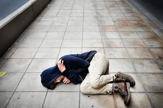 Guy in a hoodie fetal position on the floor