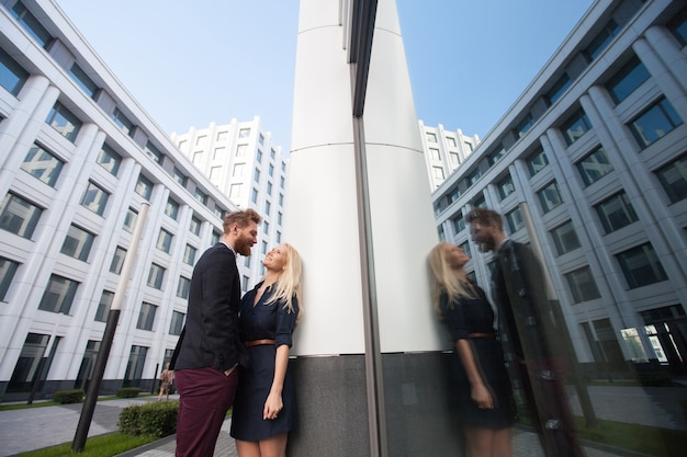 건물의 배경에 도시에서 여자를 포옹하는 사람. 유리에 반사
