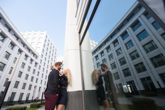 Парень обнимает девушку в городе на фоне зданий. отражение в стекле